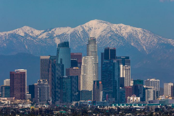 Snow is seen on the San Gabriel Mountains beyond downtown Los Angeles under a clear sky after weeks of storms and reduced tra