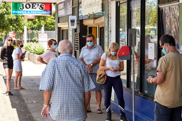 People wearing masks wait in line at a Narrabeen seafood shop on December 23, 2020 in Sydney,