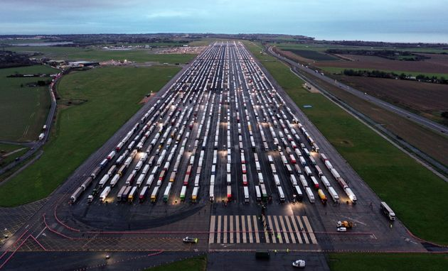 An aerial view shows lines of freight lorries and heavy goods vehicles parked on the tarmac at Manston...