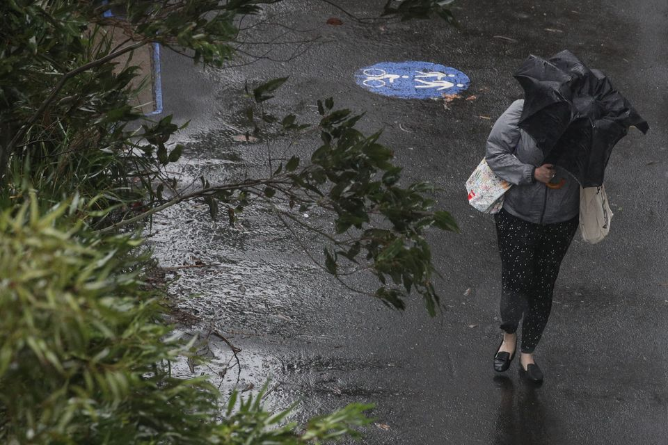 A pedestrian braves strong wind and rain in Sydney, New South Wales, February 9,