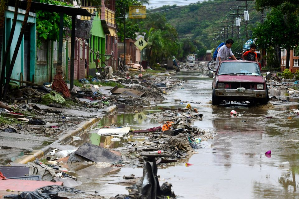 A group of people on a car drive through a mud-covered street with debris caused by Hurricane Iota's...
