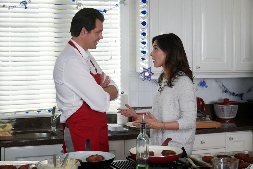 "Kristoffer Polaha and Carly Pope make latkes in ""Double Holiday."""