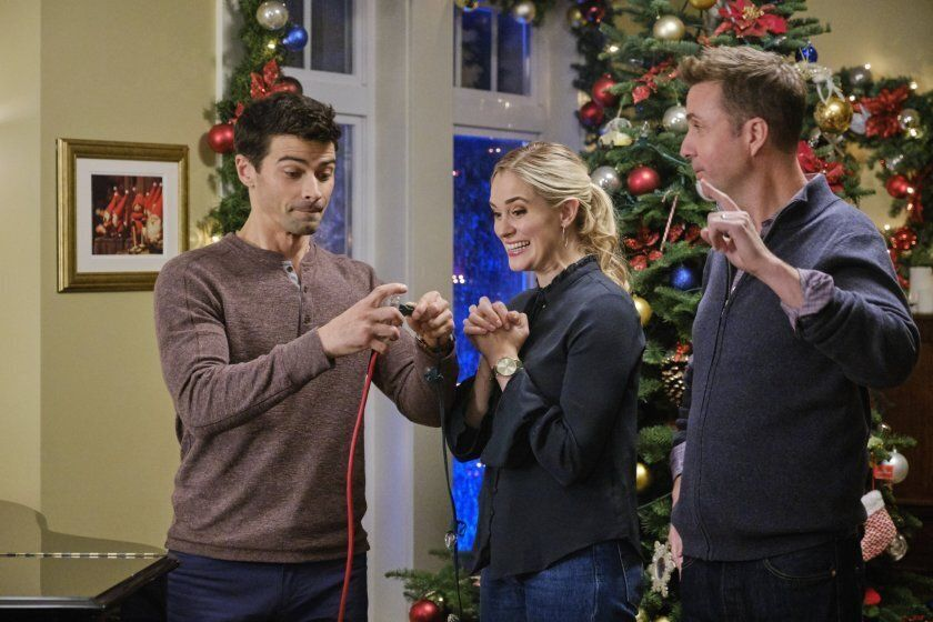 "A scene from Hallmark's ""Holiday Date,"" in which Joel is attempting to turn on the Christmas lights."