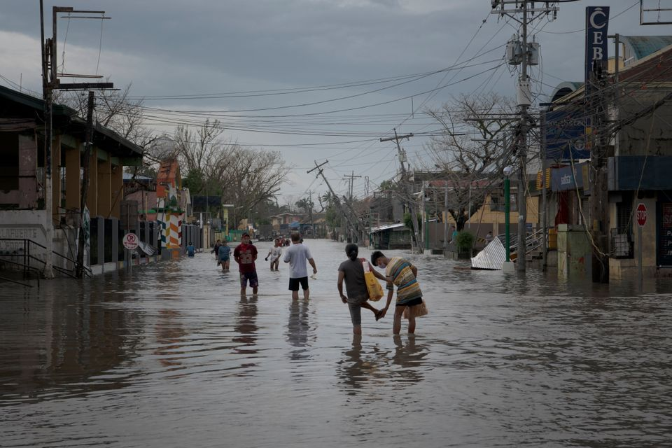 Residents wade through a flooded street in the aftermath of Super Typhoon Goni on November 2 in...