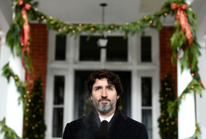Festive garlands hang from the pillars of Rideau Cottage as Prime Minister Justin Trudeau speaks during a news conference on Dec. 23, 2020.