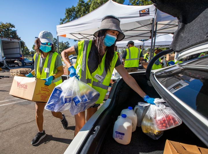 Volunteer Anh Tonnu (left) and sister Tomi Tonnu load a car in Fountain Valley, California, with food on Oct. 14 as part of S