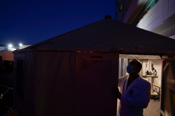 Dr. Jim Keany, an emergency medicine specialist, shuts the door of a triage tent set up to treat COVID-19 patients at Mission
