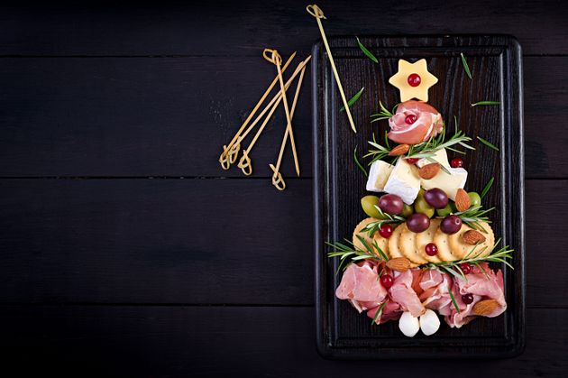 Antipasto platter with ham, prosciutto, salami, cheese, crackers and olives on a wooden background. Christmas...