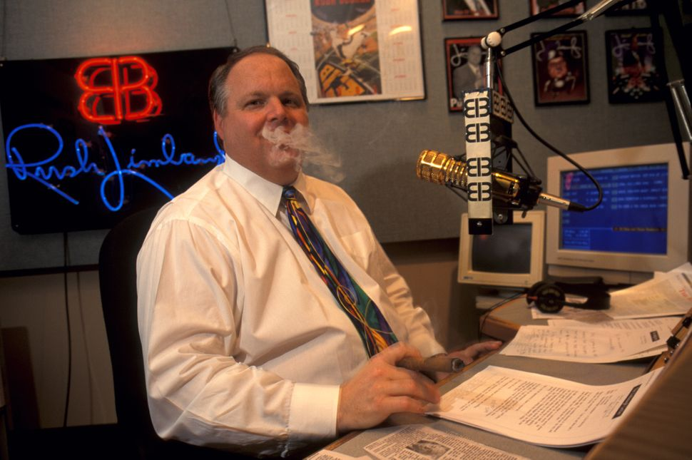 Rush Limbaugh smoking a cigar while taping his radio show.