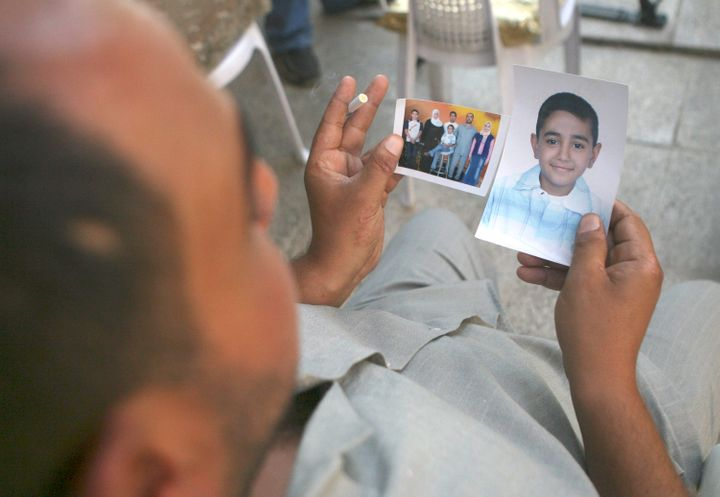 Mohammed Hafiz looks at photos of his 10-year-old son in Baghdad on Oct. 4, 2007. The boy died after the attack on Iraqi civi