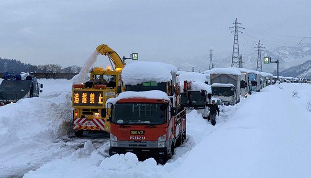 大雪により関越自動車道上り線塩沢石打インター手前で立ち往生した車両の列。左は除雪車=12月18日、新潟県南魚沼市