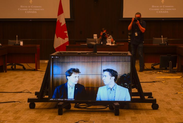 Marc Kielburger, screen left, and Craig Kielburger, screen right,  appear as witnesses via videoconference during a House of Commons finance committee in the Wellington Building in Ottawa on July 28, 2020.