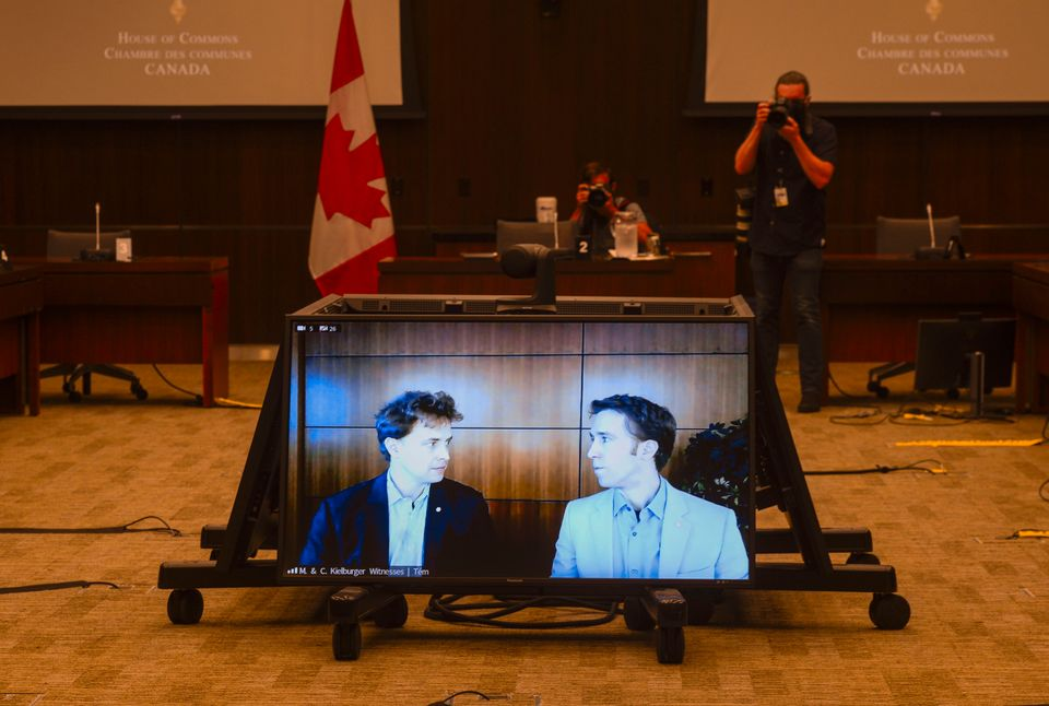 Marc Kielburger, screen left, and Craig Kielburger, screen right, appear as witnesses via videoconference...