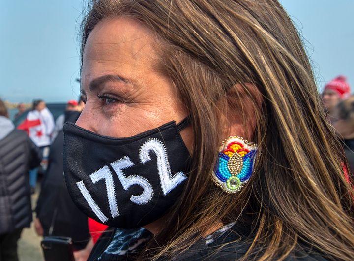 A woman wears a face mask honouring the Treaty of 1752 as members of the Sipekne'katik First Nation and others attend a ceremony on the wharf in Saulnierville, N.S., to bless the fleet before it launches its own self-regulated fishery on Sept. 17, 2020.