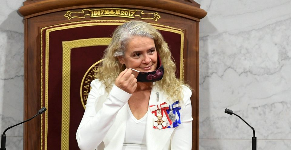 Gov. Gen. Julie Payette removes her face mask before delivering the throne speech in the Senate chamber...