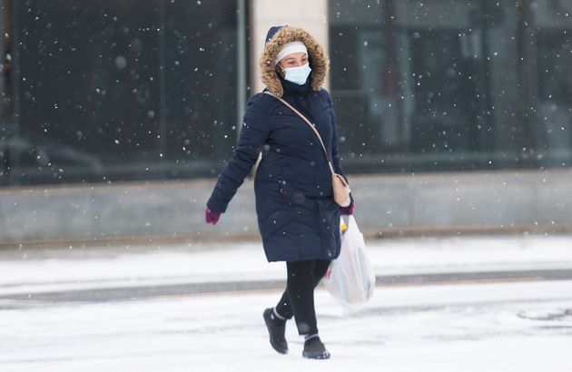 A woman wears a face mask as she crosses a street on Boxing Day in Montreal on