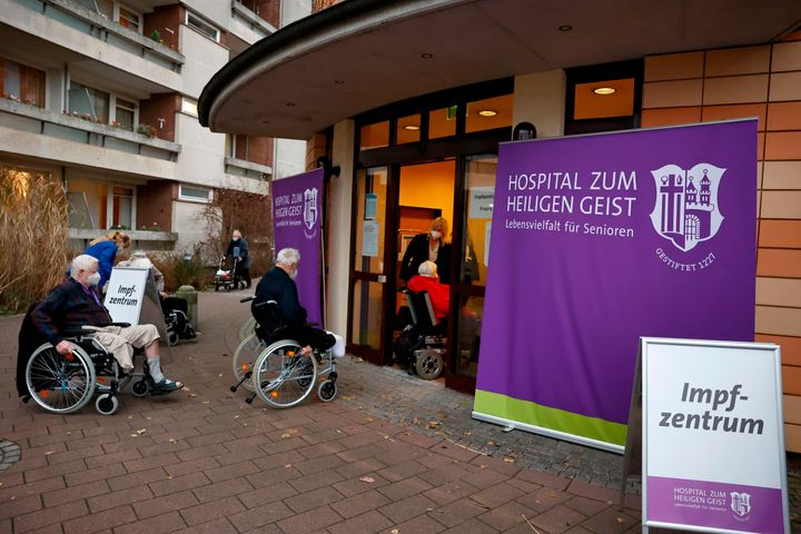Residents of the 'Hospital zum Heiligen Geist' retirement home queue to enter the local vaccination center to be inoculated w