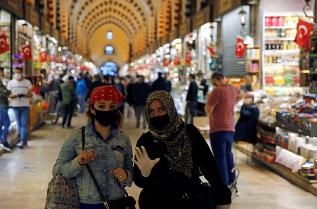 Women wearing protective face masks walk at the spice market, also known as the Egyptian Bazaar, as it...