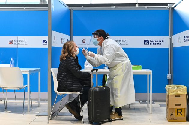 A woman, passenger who just landed from New York on an Alitalia flight, undergoes a rapid antigen swab...