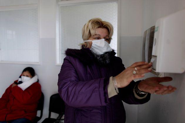 Una mujer con mascarilla como precaución contra el gel