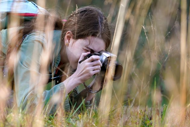 Olivia Chaffin takes photographs in a wooded area as she works on a Girl Scout photography merit badge...