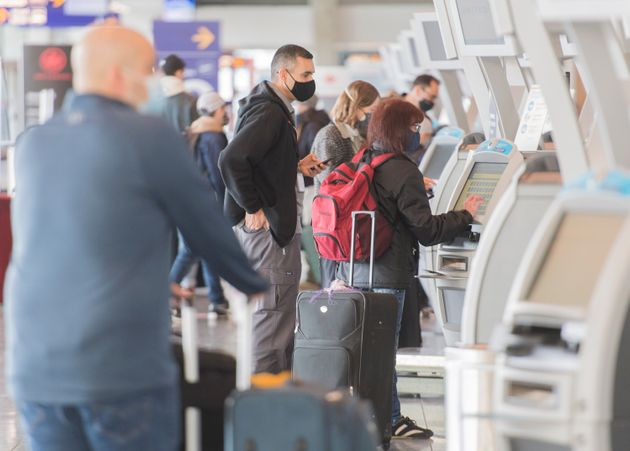 Passengers check-in using self-service desks at Montreal Trudeau International Airport in Montreal, Saturday,...