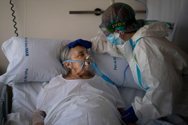 La enfermera Marta Fernández consuela a María Teresa Argullos Bove, de 94 años,...