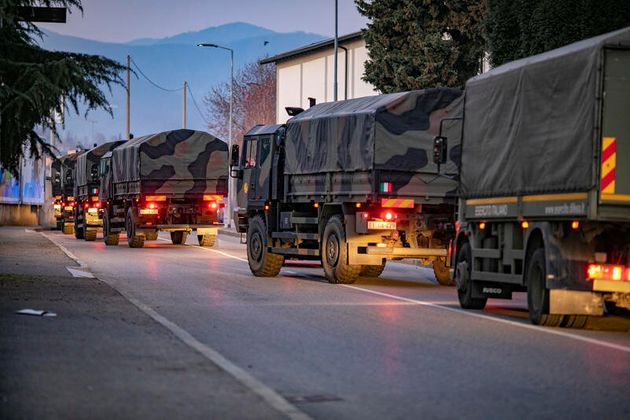 Italian military trucks drive through streets of Bergamo after the army were deployed to move coffins...