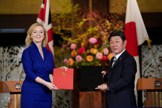 Trade secretary Liz Truss, left, and Japanese foreign minister Toshimitsu Motegi exchange agreement documents...