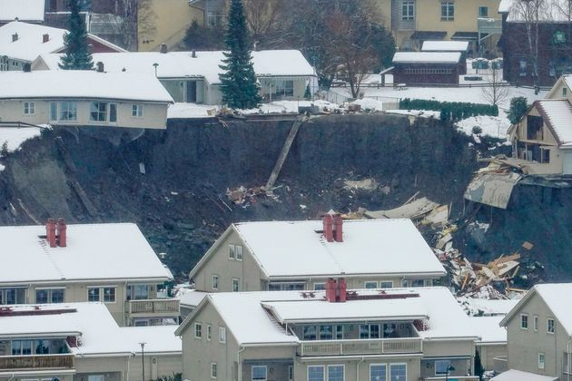 Destroyed houses are seen in a crater left behind by a landslide in the town of Ask, Gjerdrum county,...