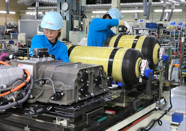 Workers at Toyota Motor Corp. set hydrogen-stored tanks, in yellow, to be placed into a fuel cell vehicle...