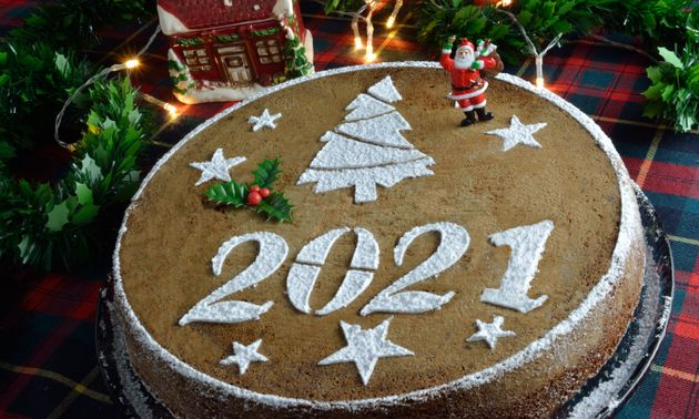 Concept with traditional Greek new years cake,vasilopita, decorative with a mistletoe and a saint claus,...
