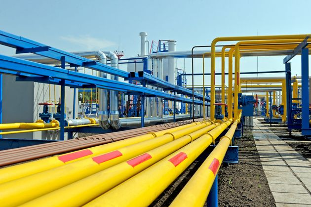 Yellow gas pipes in natural gas treatment plant in bright sunny summer