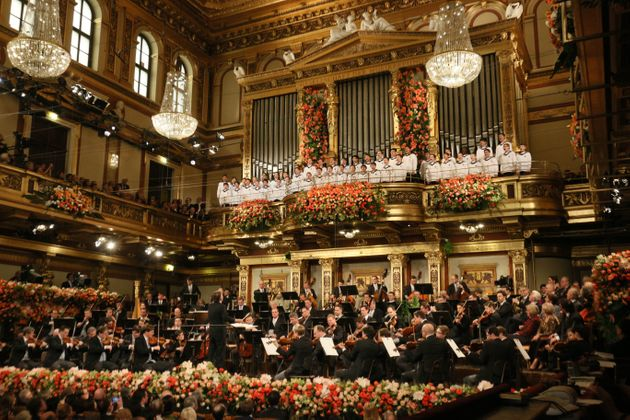 The Vienna Philharmonic Orchestra, bottom and the Vienna Boys' Choir, top, perform during the traditional...