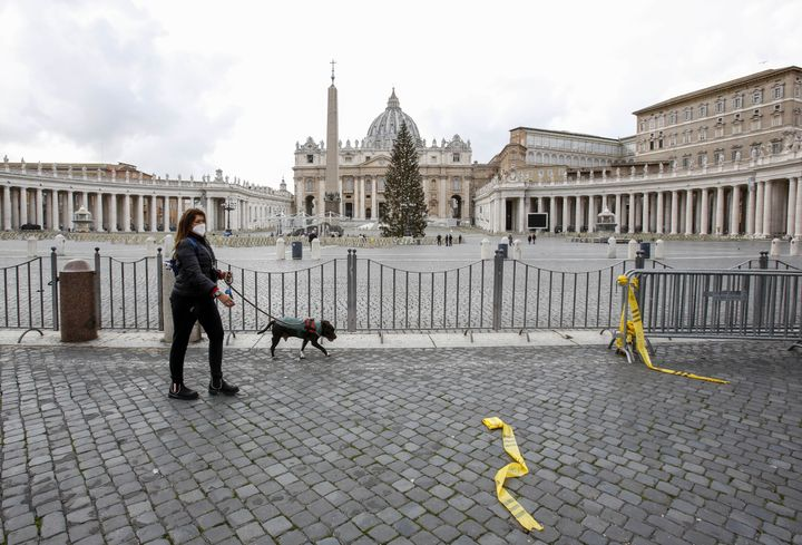 A woman wearing a face mask walks with her dog outside of an empty St. Peter's Square at the Vatican, December 25, 2020.&nbsp