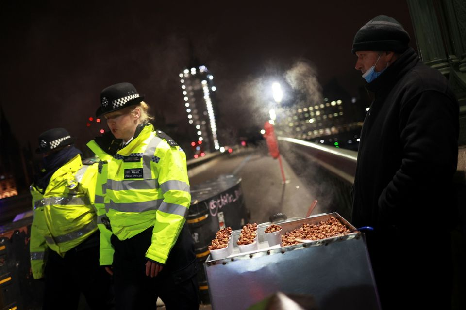 Police officers walk past a street vendor selling nuts on Westminster