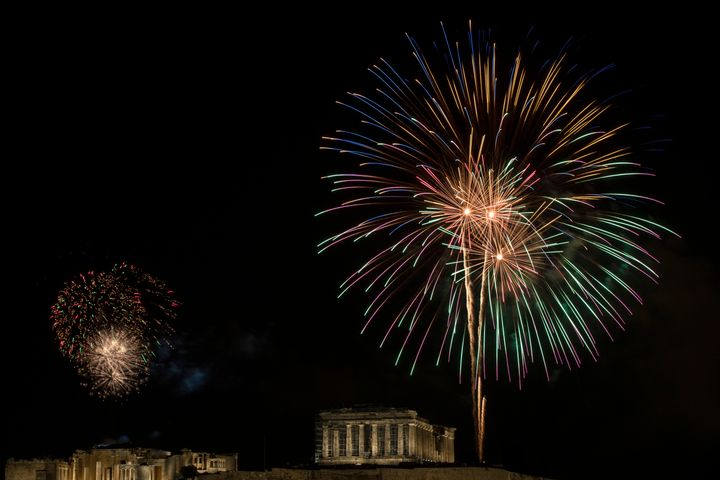 Fireworks explode over the ancient Acropolis hill with the Parthenon temple on the right and the Propylea on the left during