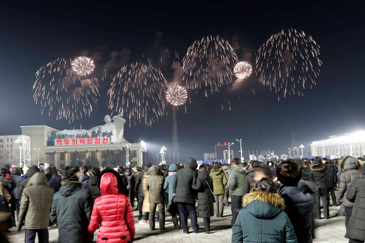 A fireworks display decorates the night sky to celebrate the New Year, as crowds of people look on, at Kim Il Sung Square in