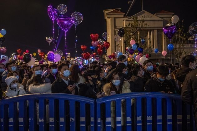 epa08913230 People gather in a street to celebrate the New Year in Wuhan, China, 31 December 2020. Life...