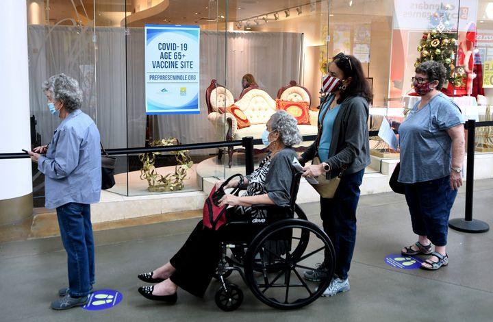 People wait in a line on New Year's Eve to receive a COVID-19 vaccination at a site for seniors in an unoccupied store at the