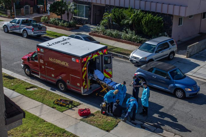 County of Los Angeles paramedics examine a potential Covid-19 patient sitting on the sidewalk before transporting him to a ho