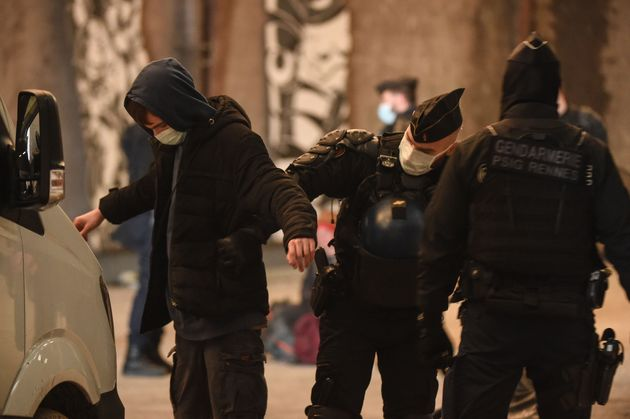 French Gendarmes pat down a reveller after breaking up a rave near a disused hangar in