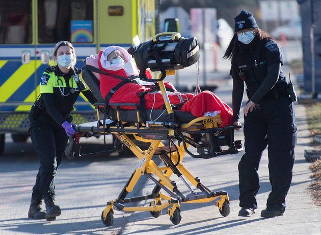 Des ambulanciers transfèrent une personne d'une ambulance à un hôpital de Montréal,...