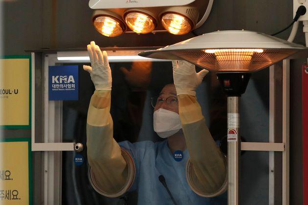 영하권의 추위 속에 서울의 한 임시 선별진료소에서 의료진이 장갑을 낀 채 잠시 손을 녹이고 있다. 2020년