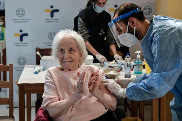Una mujer de la tercera edad aplaude al recibir una vacuna en un asilo de ancianos en Atenas, el lunes...
