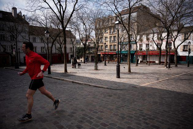 Un homme fait son footing Place du Tertre, à Paris, le 22 mars 2020, au sixième jour du premier confinement...
