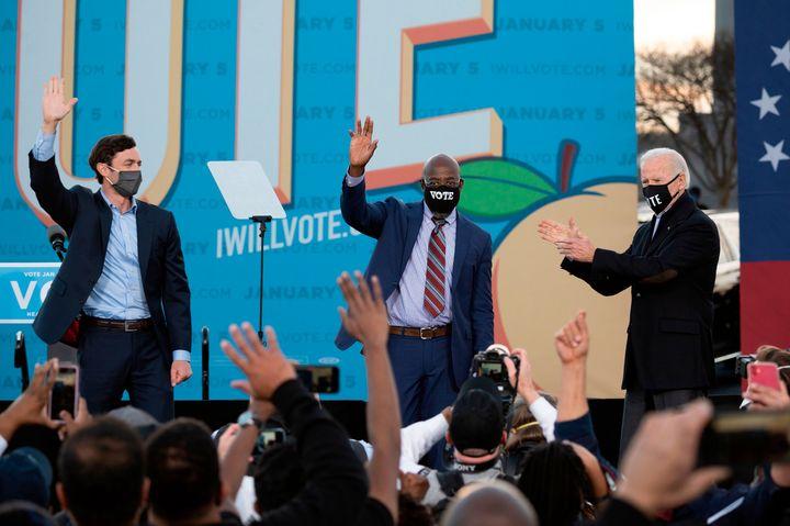 Democratic candidates for Senate Jon Ossoff (L), Raphael Warnock (C) and President-elect Joe Biden (R) stand on stage during