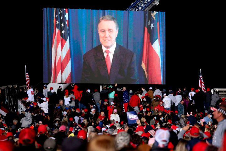 Republican incumbent senator David Perdue speaks via video monitor during a rally ahead of a Senate runoff in Dalton, Georgia