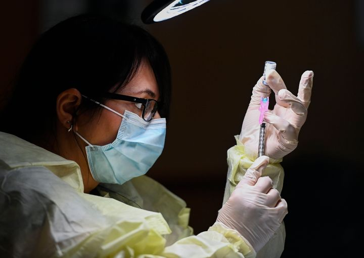 Francesca Paceri, a registered pharmacist technician carefully fills the Pfizer-BioNTech COVID-19 mRNA vaccine at a vaccine clinic  in Toronto on Dec. 15, 2020.