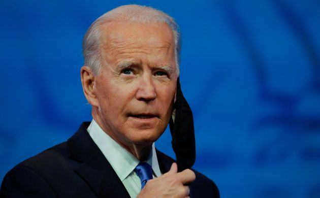 U.S. President-elect Joe Biden takes off his protective face mask to deliver a televised address to the...